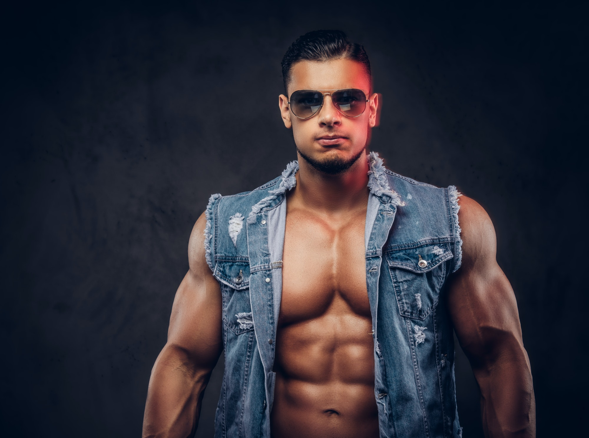 Fashionable athletic man poses in a studio.